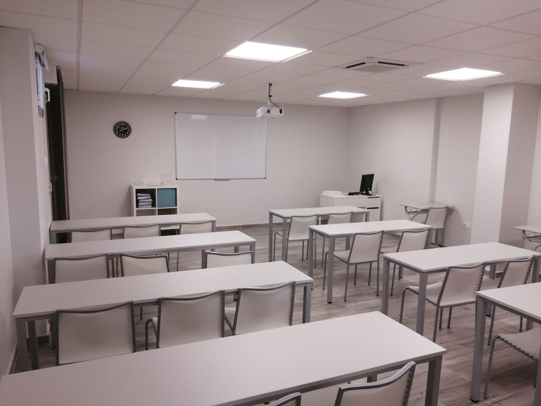 Fotografía de la derecha del aula con sillas blancas