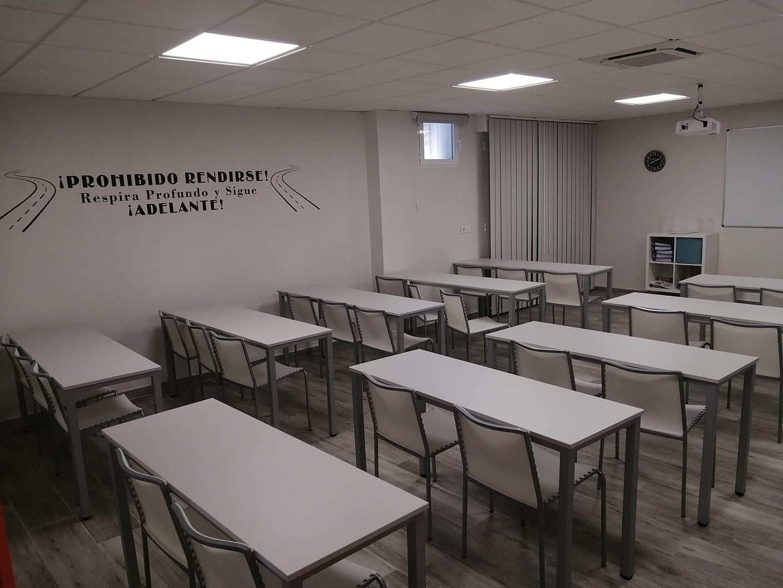 Fotografía de la izquierda del aula con sillas blancas