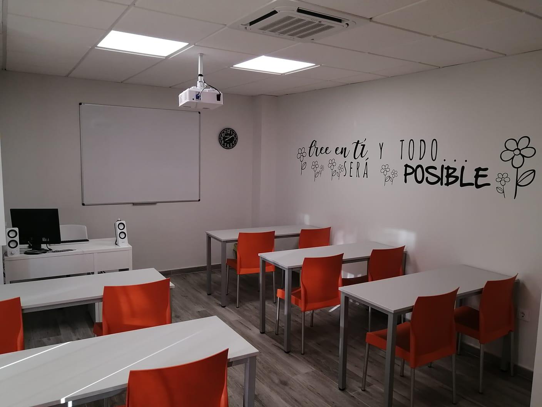 Fotografía de la derecha del aula con sillas naranjas